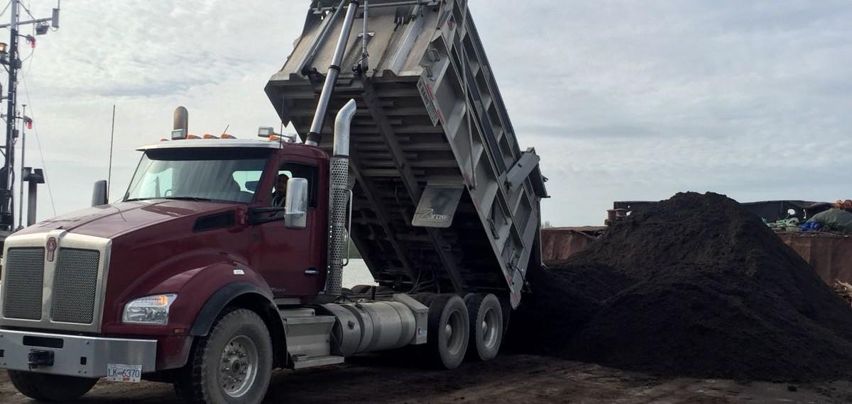 Soil being loaded onto a barge, headed for Haida Gwaii